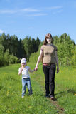 Young woman walks with daughter near green forest Stock Image