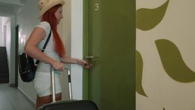 Young happy woman enters with a suitcase in her hotel room. Young woman walks down the corridor with a suitcase and enters her new apartment stock footage