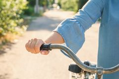 Young woman walks on foot and holds the wheel of an old bicycle on a country road in the rays of the setting sun Royalty Free Stock Images