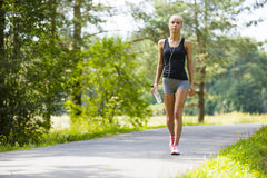 Young woman walks outdoor as workout. Beautiful young and fit blonde woman walking on trail in the woods. Workout outdoor Stock Photos