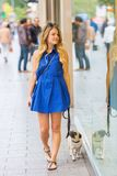 Young woman walks with a pug along shop windows Stock Photo
