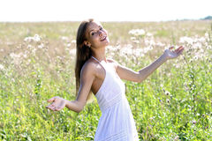 Young woman walks in summer field Royalty Free Stock Image