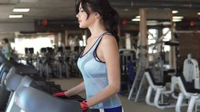 Young woman walks on a treadmill at the gym. cardio exercises in the gym. Girl running on the treadmill in the fitness room. young woman doing aerobic exercises stock footage