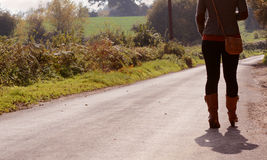 Young woman walks up a country lane alone Stock Photography