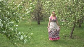 Walk in the spring park. A young woman walks up to a flowering tree, she sniffs it and then leaves stock video