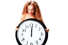 Young woman with a wall clock Royalty Free Stock Photos