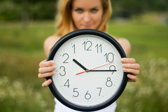 Young woman with a wall clock Royalty Free Stock Photo