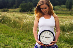Young woman with a wall clock Royalty Free Stock Photography