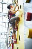 Young woman on the wall in rock-climbing center Stock Photography