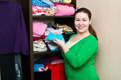 Young woman in the wardrobe. Young caucasian woman in the wardrobe packs things on a shelfs Stock Photos