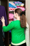 Young woman and wardrobe. Young caucasian woman thinking about to put on near wardrobe Stock Photos