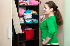 Young woman and wardrobe. Young caucasian woman thinking about to put on near wardrobe Royalty Free Stock Photos