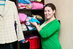 Young woman in the wardrobe. Young caucasian woman in the wardrobe packs things on a shelfs Royalty Free Stock Photo