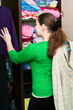 Young woman in the wardrobe. Young caucasian woman thinking about to put on near wardrobe Stock Photo