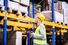 Woman warehouse worker with tablet. Young woman warehouse worker with tablet. A supervisor controlling stock Royalty Free Stock Photos