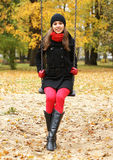 A young woman in warm clothes playing in a park Royalty Free Stock Photos