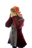 Young woman in warm clothing and peeking through her fingers Stock Image