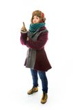 Young woman in warm clothing and pointing upward Stock Images