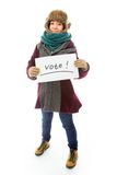 Young woman in warm clothing and showing vote sign on white back Royalty Free Stock Photo
