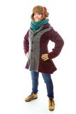Young woman in warm clothing and standing with her arms akimbo Royalty Free Stock Photography
