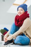 Young woman in warm hand knitted hat at home Stock Images