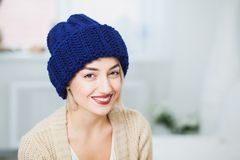 Young woman in warm hand knitted hat at home Royalty Free Stock Photo