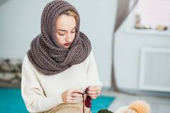 Young woman in warm hand knitted snood scarf at home Stock Photo