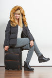 Young woman in warm jacket with suitcase. Royalty Free Stock Photo