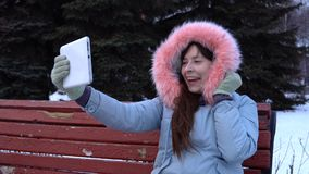 A young woman in a warm jacket uses a digital tablet in the park in the winter. Young attractive woman grabs a selfie digital tablet while sitting on a bench in stock video