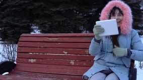 A young woman in a warm jacket uses a digital tablet in the park in the winter. A young woman freelancer in a gray warm coat sits on a bench, uses a digital stock video footage