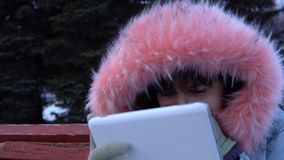 A young woman in a warm jacket uses a digital tablet in the park in the winter. Portrait of a young happy woman sneezes uses a digital tablet and sitting on a stock footage