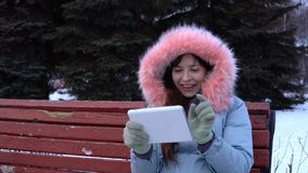 A young woman in a warm jacket uses a digital tablet in the park in the winter. A young happy woman in a gray warm coat sits on a bench and uses a digital stock video footage