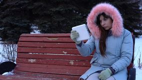 A young woman in a warm jacket uses a digital tablet in the park in the winter. A young sad, upset woman in a gray warm coat sits on a bench, uses a digital stock video footage