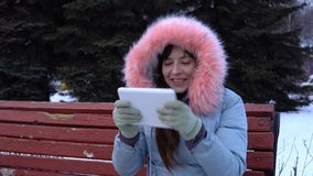 A young woman in a warm jacket uses a digital tablet in the park in the winter. A young woman freelancer in a gray warm coat sits on a bench, uses a digital stock video