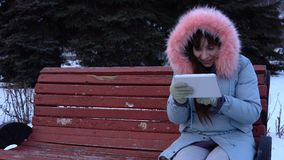 A young woman in a warm jacket uses a digital tablet in the park in the winter. A young woman in a gray warm coat sits on a bench and uses a digital tablet, it` stock footage