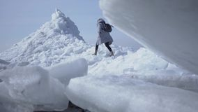 Young woman in warm jacket walking on the glacier. Amazing nature of a snowy North or South Pole. The brave female polar