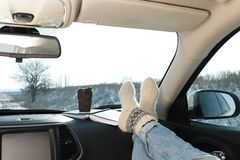 Young woman in warm socks holding her legs on car. Cozy atmosphere. Young woman in warm socks holding her legs on car dashboard. Cozy atmosphere royalty free stock images