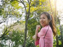 Young woman warm up her body by stretching her arms to be ready for exercising and do yoga in the park. Royalty Free Stock Images