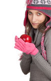 Young woman in warm winter hat with apple Stock Photos