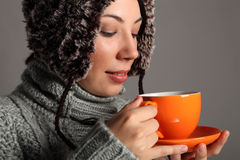 Young woman in warm winter hat drinking hot tea Stock Photography
