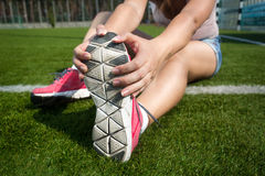 Young woman warming up on grass before running Stock Photo