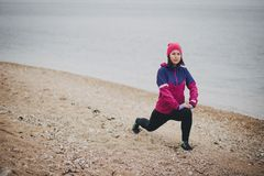 Young woman warming up before jogging at the beach. Beautiful young woman wearing duffle warming up before jogging at the beach Royalty Free Stock Image