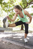 Young Woman Warming Up With Stretches On Park Bench Stock Photography