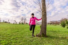 Young woman warming up and stretching the legs before running on a cold winter, autumn of fall day in an urban park. royalty free stock photos