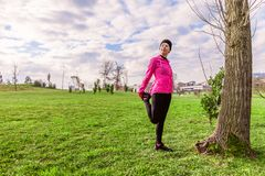 Young woman warming up and stretching the legs before running on a cold winter, autumn of fall day in an urban park. royalty free stock photography