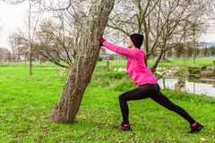 Young woman warming up and stretching the legs before running on a cold winter, autumn of fall day in an urban park. royalty free stock photo