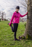 Young woman warming up and stretching the legs before running Royalty Free Stock Image