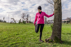 Young woman warming up and stretching the legs before running Royalty Free Stock Images