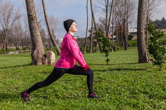Young woman warming up and stretching before running. Young woman warming up and stretching the legs before running on a cold winter day in an urban park Stock Photography