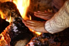 Girl warm her hands over fire in winter stock photography